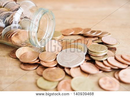 Coins spilling out of a glass bottle Money for income and expenditure and tax selective focus