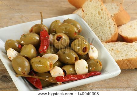 dish of green olives wit sweet garlic and jalapeno peppers