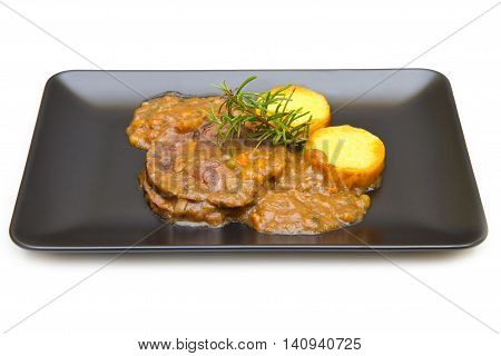 black dish with braised meat with polenta on white