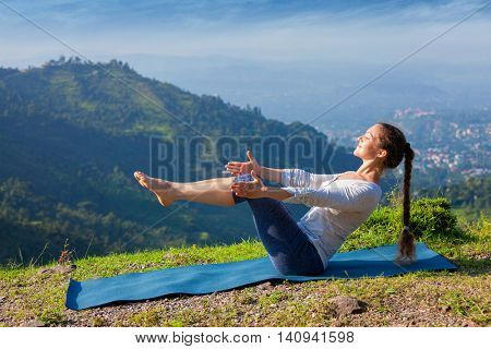 Yoga outdoors - young sporty fit woman doing Ashtanga Vinyasa Yoga asana Navasana - boat pose easy beginner variation - in Himalayas mountains in the morning  Himachal Pradesh, India