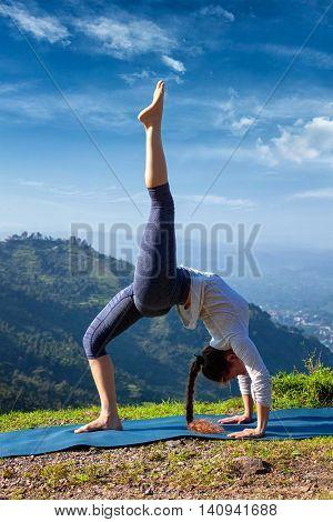 Yoga outdooors - woman doing yoga asana eka pada urdva dhanurasana Upward Bow Pose back benkd outdoors in Himalayas in the morning