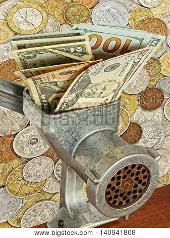 Money and business concept.Dollar banknotes in meat grinder on lot of different coins background.