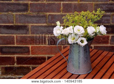 White Prairie Gentians In A Jug On A Wooden Table