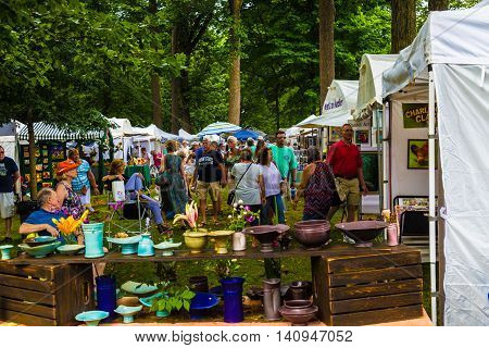 Lititz PA - July 30 2016: Hundreds of visitors stroll through the Lititz Springs Park to see the art of over 140 artists working in oils acrylics watercolor pastels drawing ceramics mixed media and sculpture at the 50th Lititz Outdoor Fine Art Show.