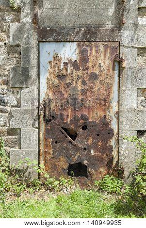 perforated rusty metallic door in sunny ambiance