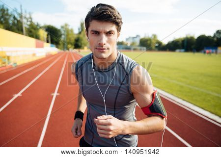 Close up portrait of a young handsome sports man running down stadium track with earphones