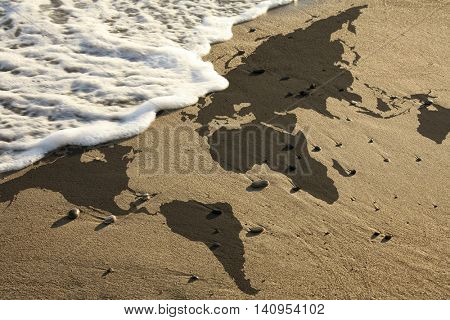elevated view of conceptual world map on beach. Furnished NASA image used for this image.