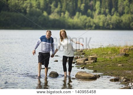 A young couple walking holding hands along the river Bank. Honeymoon.