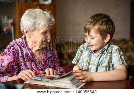 Grandma shows photo album to little grandson.