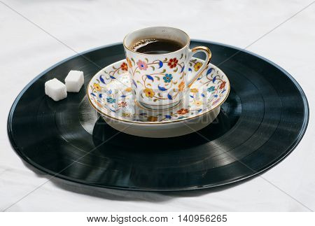 Song of a morning concept. Retro sound vinyl plate and cup of coffee with sugar on it.