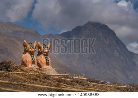 Two cow resembling porcelain incan figurines on the roof of village hut
