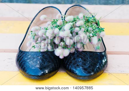 bouquet of wild flowers on the black patent leather shoes