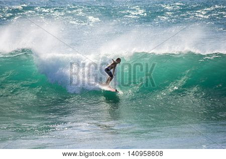 GRAN CANARIA CANARY ISLANDS - JANUARY 05 2014: Unidentified man surfing on a large wave on Playa del Ingles on the coast of Atlantic ocean Gran Canaria Canary islands Spain