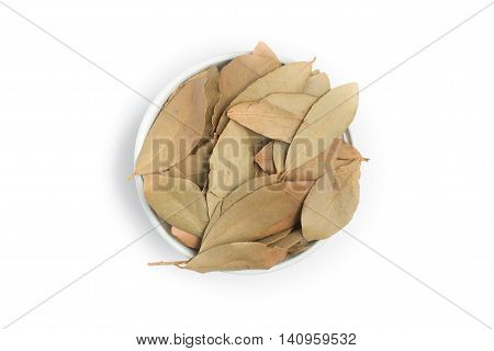 Bulk Bay Leaves into a bowl over a white background. (Laurus nobilis)