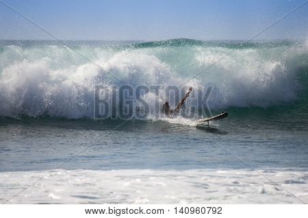 Unidentified man surfing on a large wave on Playa del Ingles on the coast of Atlantic ocean Gran Canaria Canary islands Spain