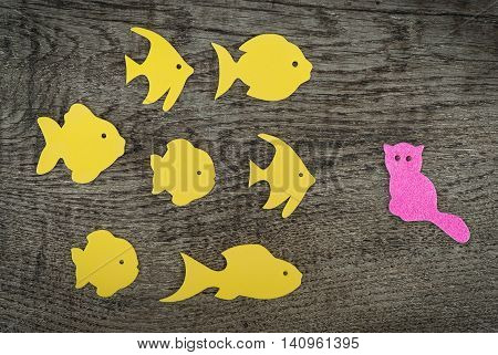 Group of yellow fish against one small cat on wooden background