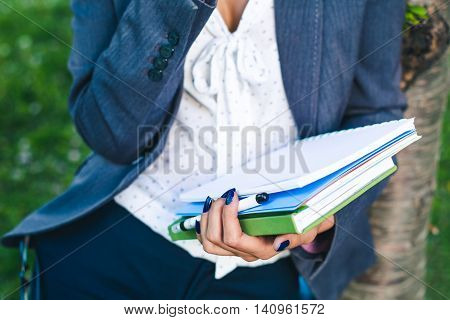 student girl with study sheets and glossary book close-up. Outdoor