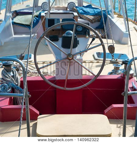 Steering wheel on the yacht with blue sea water background