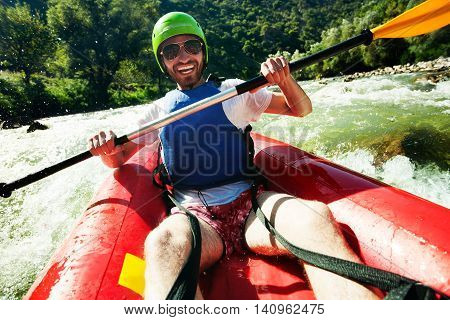 A happy young man in red inflatable canoe having fun in fast waters of a river.