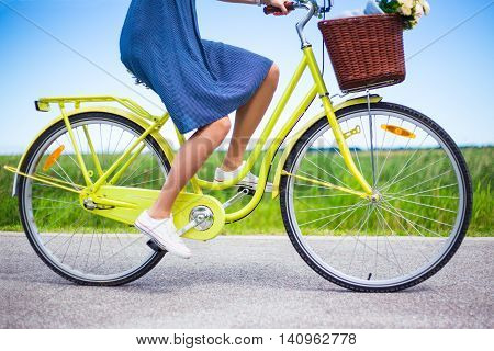 Side View Of Woman Riding Vintage Bicycle In Countryside