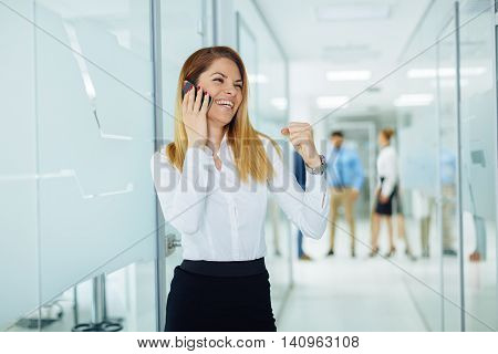 Young businesswoman on the phone with a group of people behind out of focus