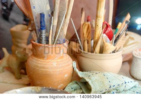 Handmade old clay pots with pencils and other stuff on the table