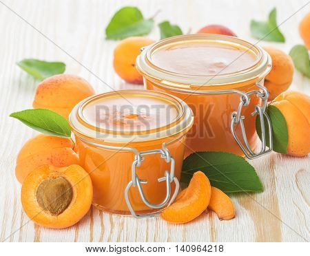 Two jars of apricot jam and fresh fruits on the white wooden background