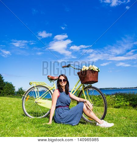 Portrait Of Happy Woman Sitting On The Grass With Vintage Bicycle On The Sea Coast Over Blue Sky Bac