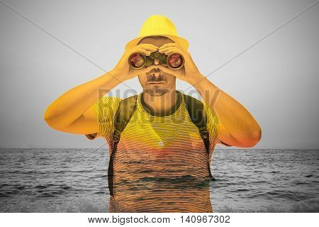 Young tourist guy looking at sunset over sea by using binoculars. Double exposure conceptual photo. Vacation concept.