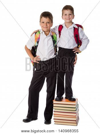 Two happy schoolboys standing with pile of books, isolated on white