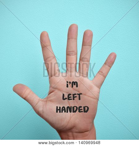 the text I am left-handed written in the palm of a left-handed man, against a blue background