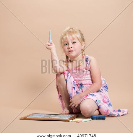 Little girl playing with chalks on her chalk board