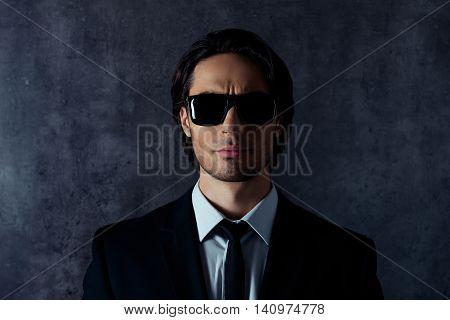Serious  Hispanic Man Holding Glasses On Gray Background