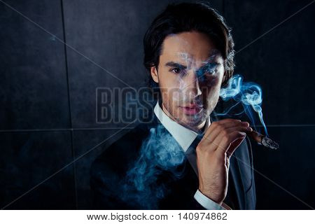 Closeup Portrait Of Brutal Handsome Man  Holding A Cigar With Smoke