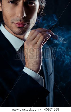 Close Up Portrait Of Brutal Man In The Smoke Holding A Cigar In Hand