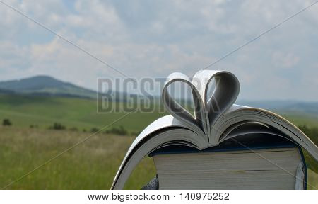 Pages Of Book In Shape Of Heart Symbol In A Landscape