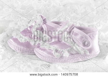 Pink baby booties on a lace background