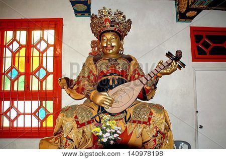 Hong Kong China - December 12 2006: Statue of a Buddha playing a stringed instrument at the Po-Lin Monastery on Lantau Island