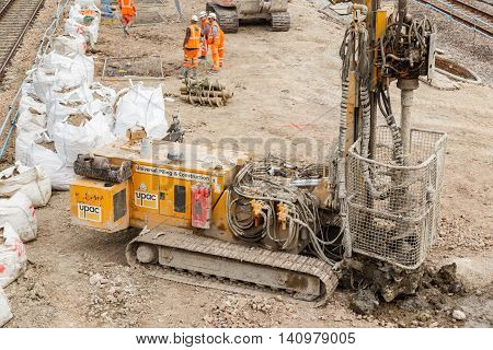 ILKESTON ENGLAND - AUGUST 1: Construction workers and pile drilling machine on site next to a section of railway track. In Ilkeston Derbyshire England. On 1st August 2016.