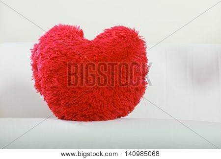 Red heart shape pillow on sofa couch. Valentines day love.