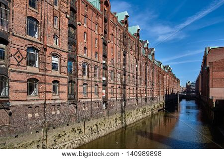 View along a waterway and old brick facade of the ancient Speicherstadt of Hamburg