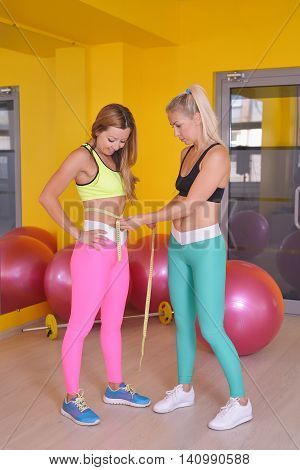 personal coach training measuring his young female client waist.