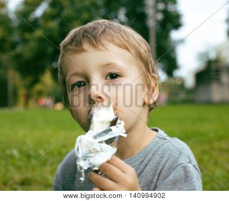 little cute boy with ice cream outside in green park, dirty face close up