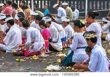 Bali,Indonesia-May,28, 2010: Balinese people with typical clothes praying on May 28, 2010 in Tanah Lot temple, Bali. The temple has been part of Balinese mythology for centuries.