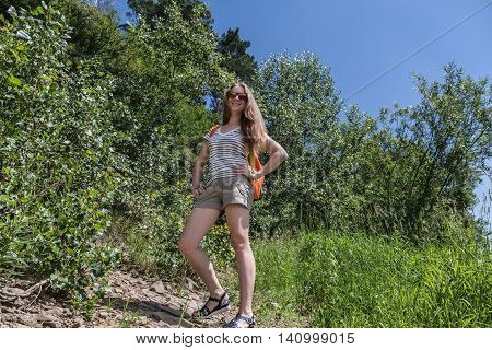 The girl with a backpack standing on a forest path