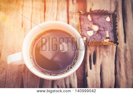 Top view of a cup of coffee on old wooden background with sunlight. Vintage picture style. Shallow depth of field (dof) selective focus. Warm tone.