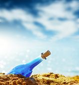 Blue glass bottle in sand and airy clouds like genie