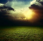 foto of storms  - Storm dark clouds over field with grass - JPG