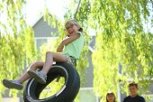pic of tire swing  - Young girl on tire swing - JPG