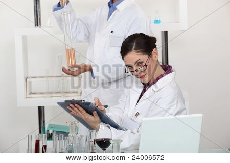 Woman taking notes in her lab.